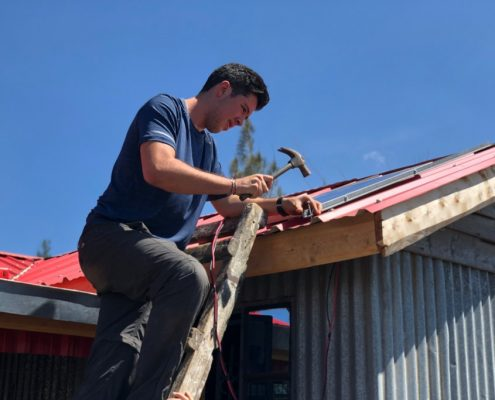 ARCC teen installing solar panels on a home in Kenya
